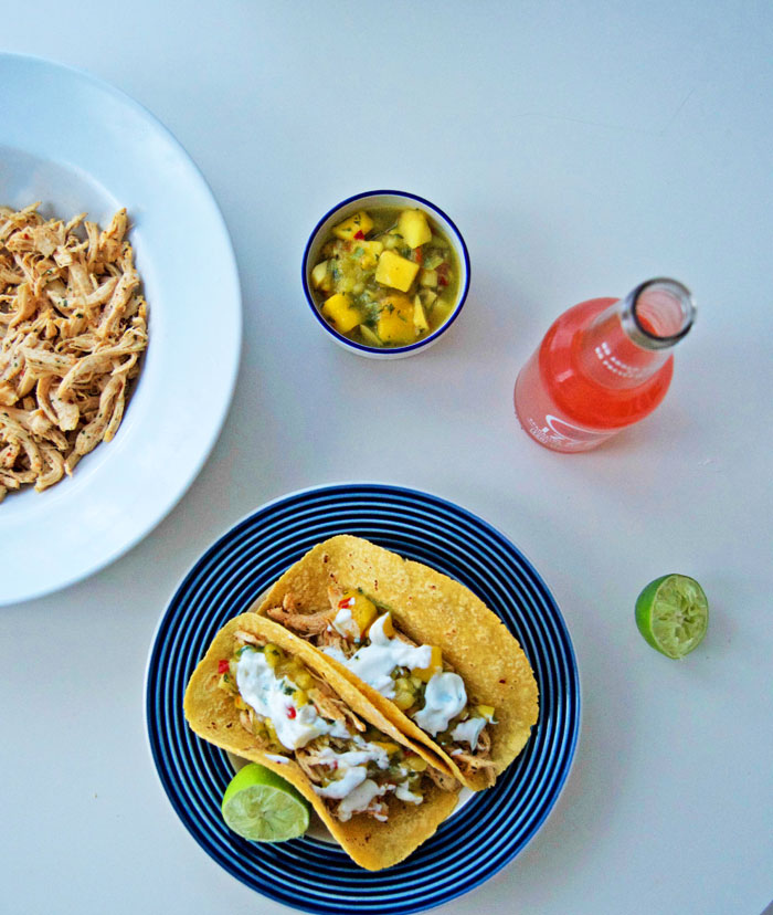 Let's taco about this dy-na-mite combo in time for Cinco De Mayo!! Pulled chicken tacos topped with pineapple mango salsa + lime crema | dcgirlinpearls.com